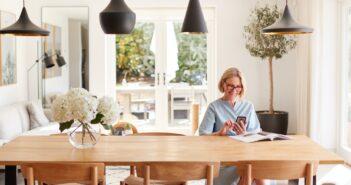 Äldre kvinna som sitter vid sitt bord hemma